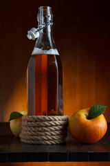 Bottle of apple cider with apples on wooden table