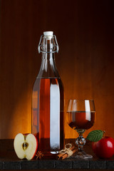 Bottle and glass of apple cider with sliced apple