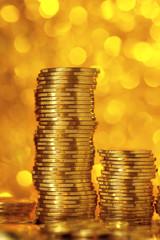 Golden coins on bright golden bokeh background