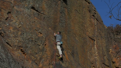 Rock climber climbs steep granite route