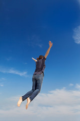 young woman jumping on the blue sky
