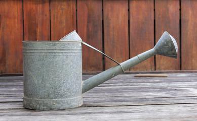 Metal watering pot side on wood floor