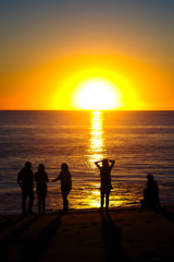 Family on the beach silhouetted by setting sun