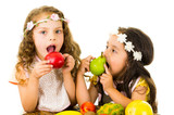 Beautiful healthy little girls eating delicious fresh fruits