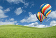 Hot Air Balloons In Beautiful Blue Sky Above Grass Field