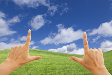 Female Hands Framing Deep Blue Sky Above Grass Field