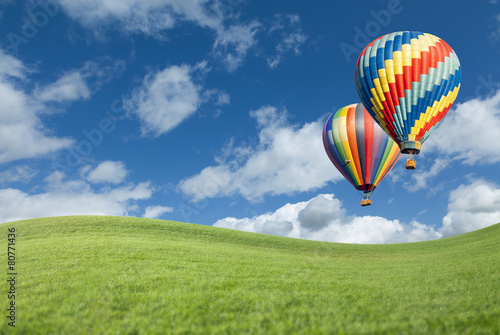 Hot Air Balloons In Beautiful Blue Sky Above Grass Field - 80771436