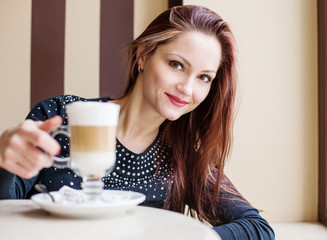 Beautiful woman drinking coffee in a cafe