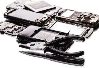 broken phones and pliers closeup