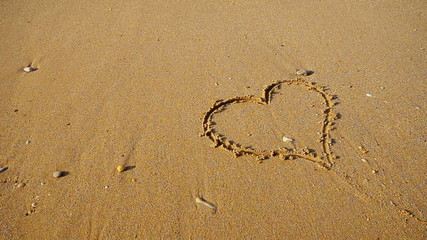 Heart symbol on the snad beach and sea waves.