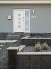 Moderne Fassade eines Einfamilienhauses mit Steingarten in grau