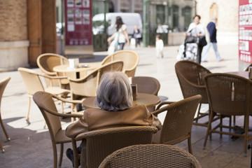 Señora mayor sentada en terraza