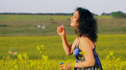 Happy woman is blowing bubbles in a field of Raps.