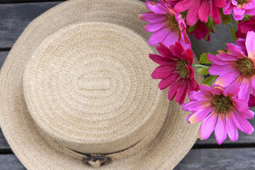 Vintage style hat and flower on wood background