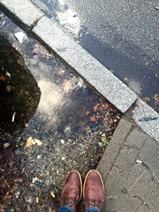 person standing next to puddle after rain