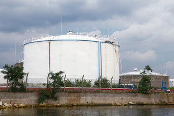 Big white oil tank on the sea coast in port