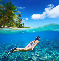 Woman floating underwater on background of islands, coral reef
