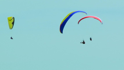 Three Paragliders Flying In The Blue Sky