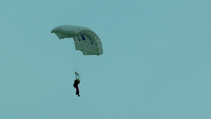 One Parachutist Landing And Hiding In Green Trees