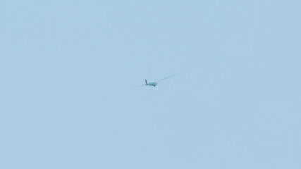 White Glider Slowly Soaring In Blue Sky