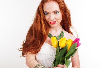 Redheaded girl with freckles is holding tulips