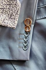 Wedding rings on the sleeve of his jacket the groom