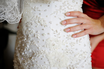 hand of bride with manicure on dress clloseup