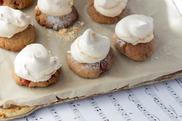 Shortbread cookies with peanut and meringues on cooking paper an