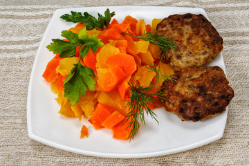 Turnip stew with carrots and cutlets on a plate