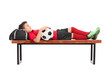 Boy in a red football jersey lying on a bench