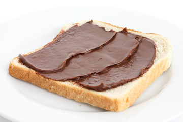 Chocolate nut spread on sliced white bread on plate.