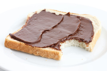 Chocolate nut spread on sliced white bread on plate. Bite mark.