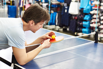 Man chooses table tennis racquet in shop