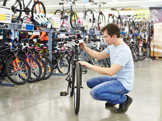 Man checks bike before buying in sports shop