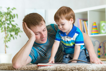 kid boy and father read a book on floor indoors