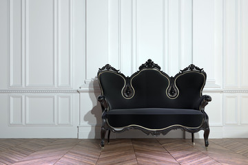 Black vintage couch against a paneled wall