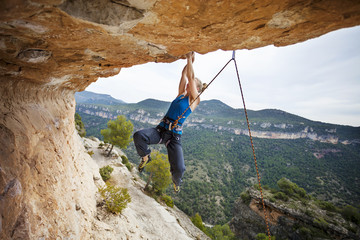Woman rock climber struggling to make next movement up