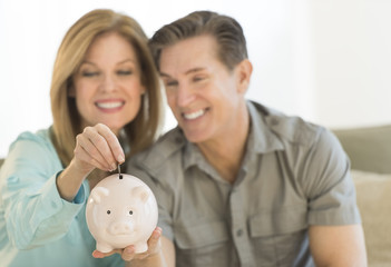 Happy Mature Couple With Piggybank At Home