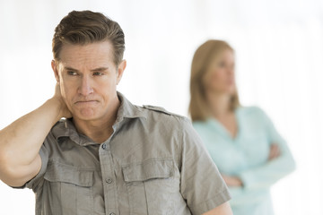 Angry Man Looking Away With Woman In Background At Home
