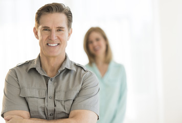 Mature Man Smiling With Woman In Background