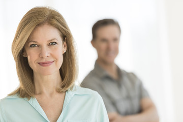 Mature Woman Smiling With Man Standing In Background