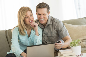 Mature Couple Using Mobile Phone And Laptop On Sofa