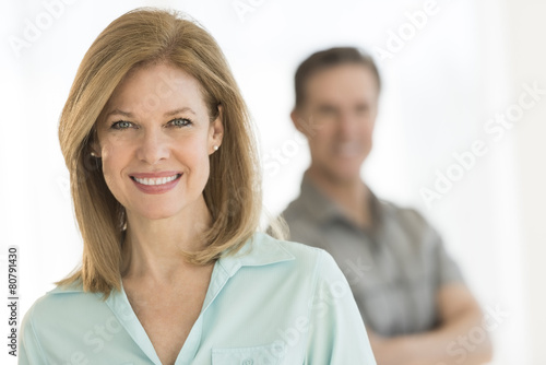 Mature Woman Smiling With Man Standing In Background Poster