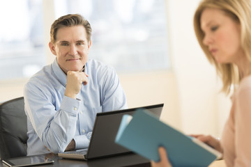Confident Businessman With Colleague In Office