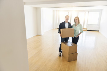 Happy Mature Couple With Cardboard Boxes In New House
