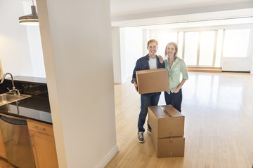 Happy Mature Couple With Cardboard Boxes At New Home