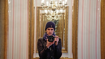 young photographer filming himself in mirror inside building at
