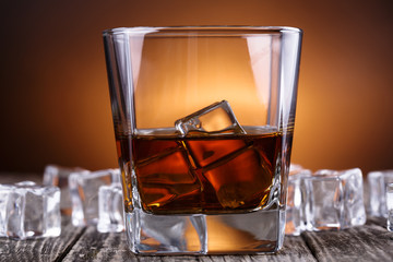 Glass of whiskey and ice on a wooden table.