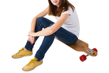 Young woman sitting on a skateboard