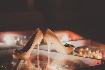 Wedding shoes with a bow on luminous floor